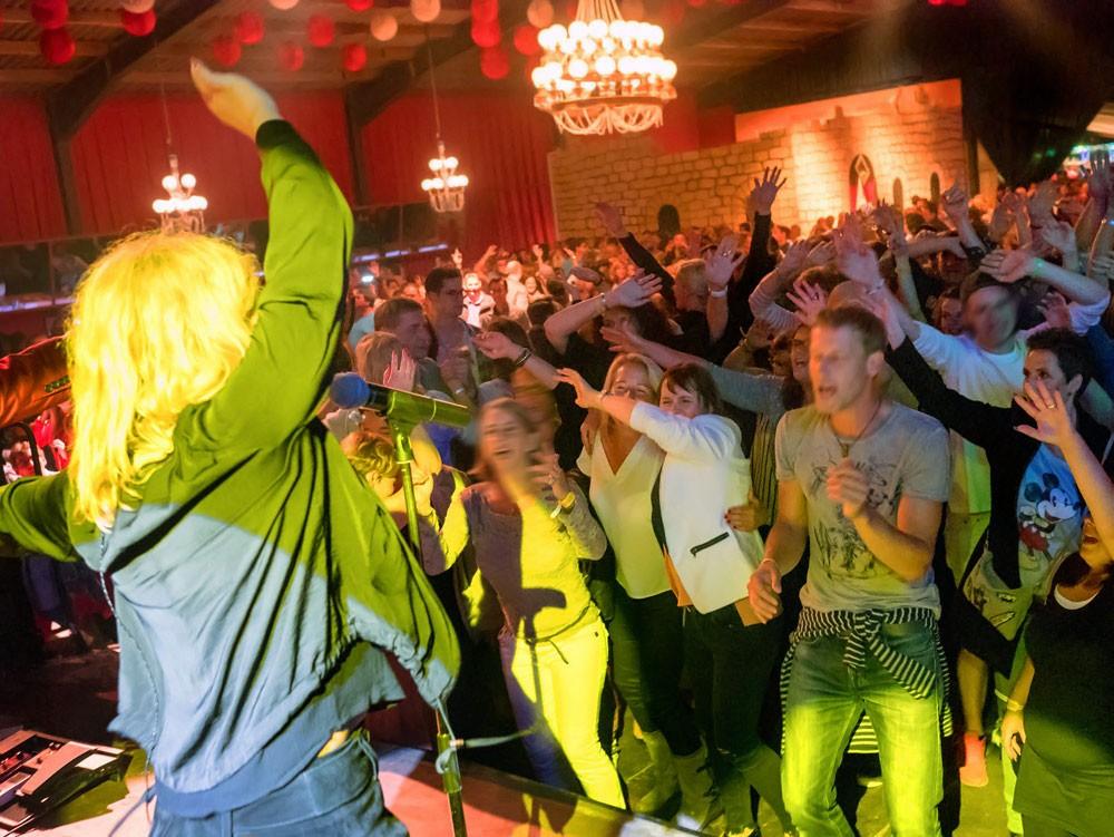feiernde menschen hände hoch sängerin live mit publikum