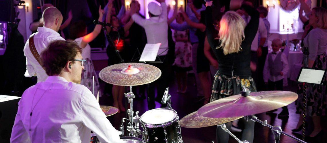 Schlagzeuer Liveband tanzende Menschen Hände hoch